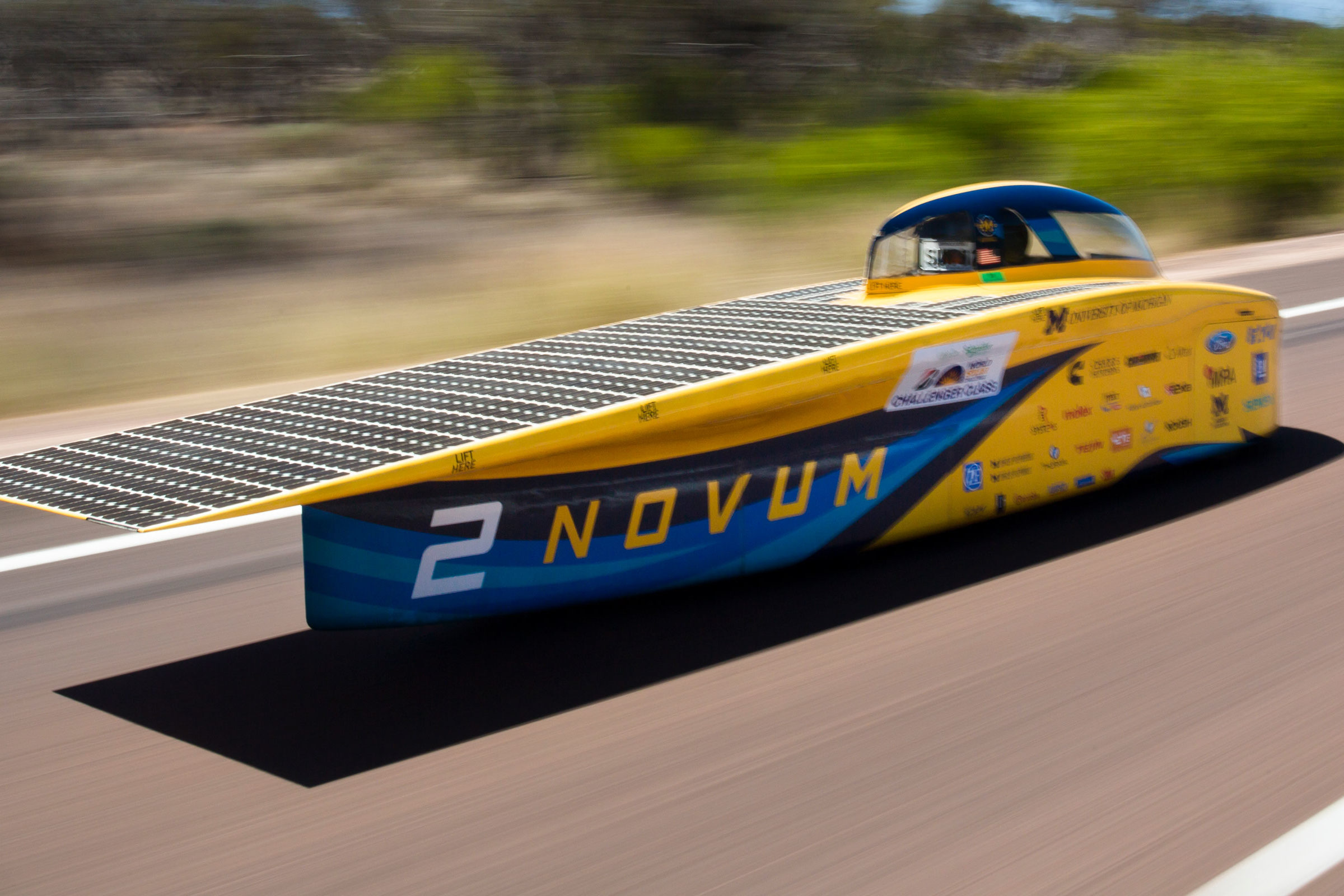 Solar car racing on road in Australia.