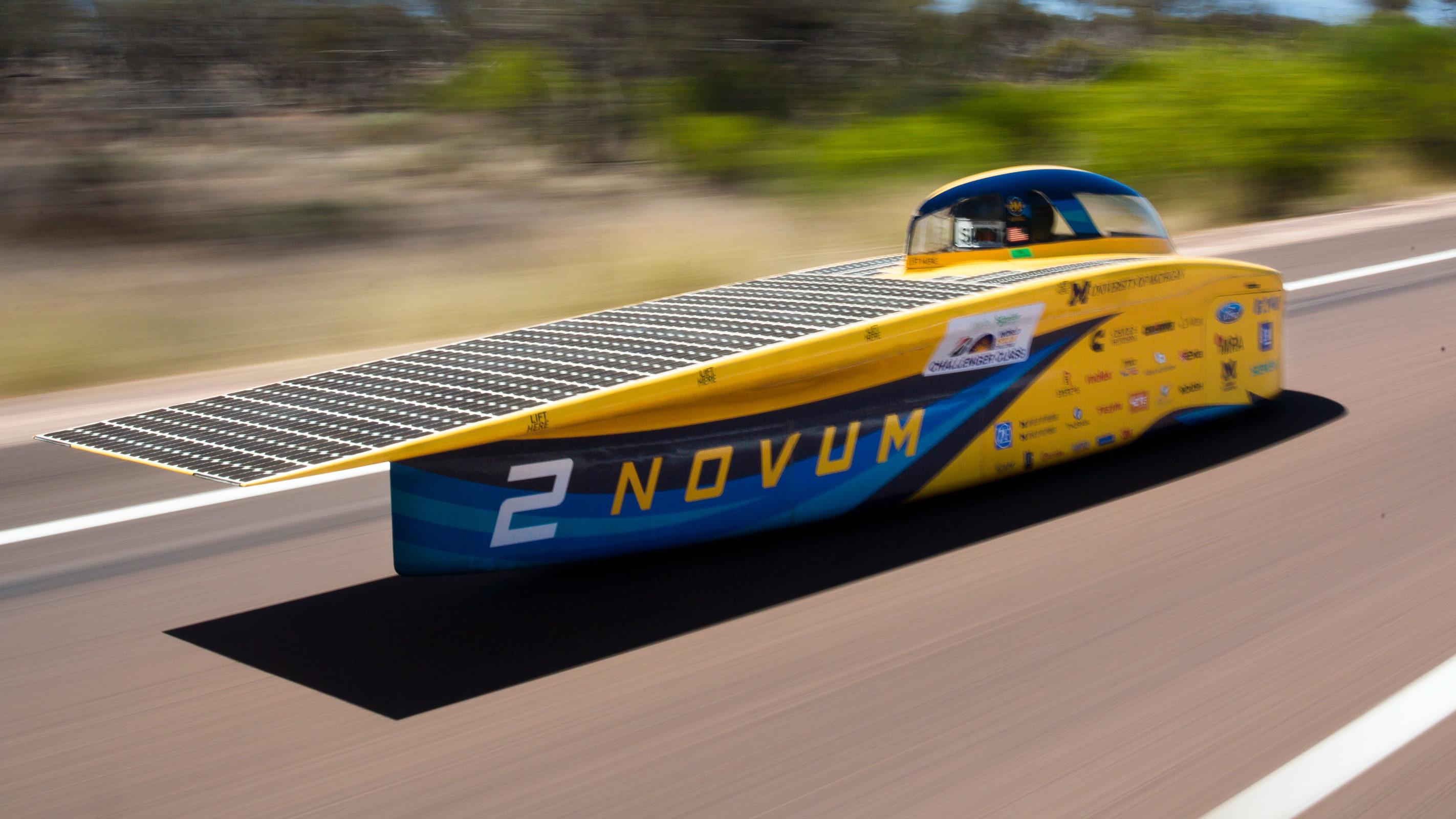 Solar car racing on road in Australia.