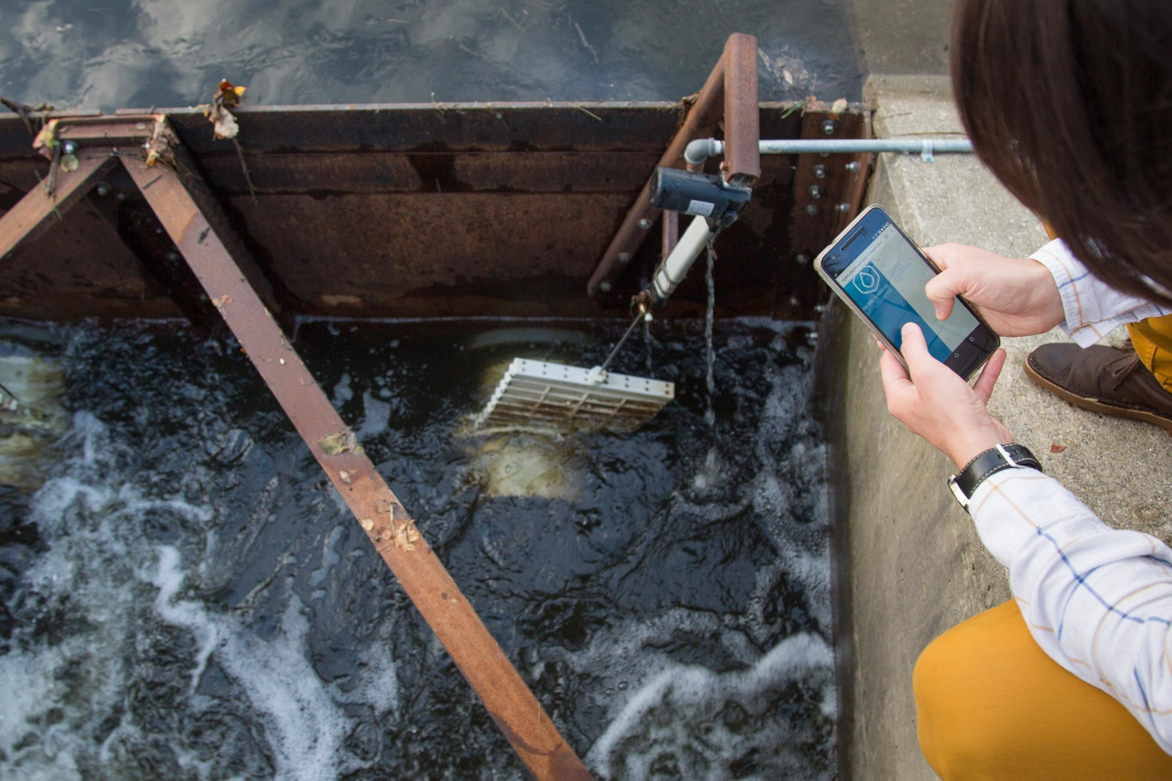 A man uses his phone to remotely control water valves