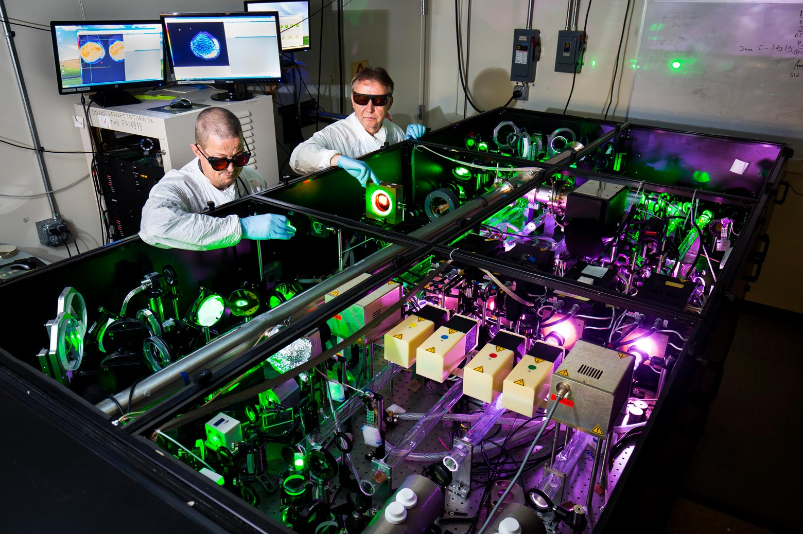 Two scientists stand next to the HERCULES laser