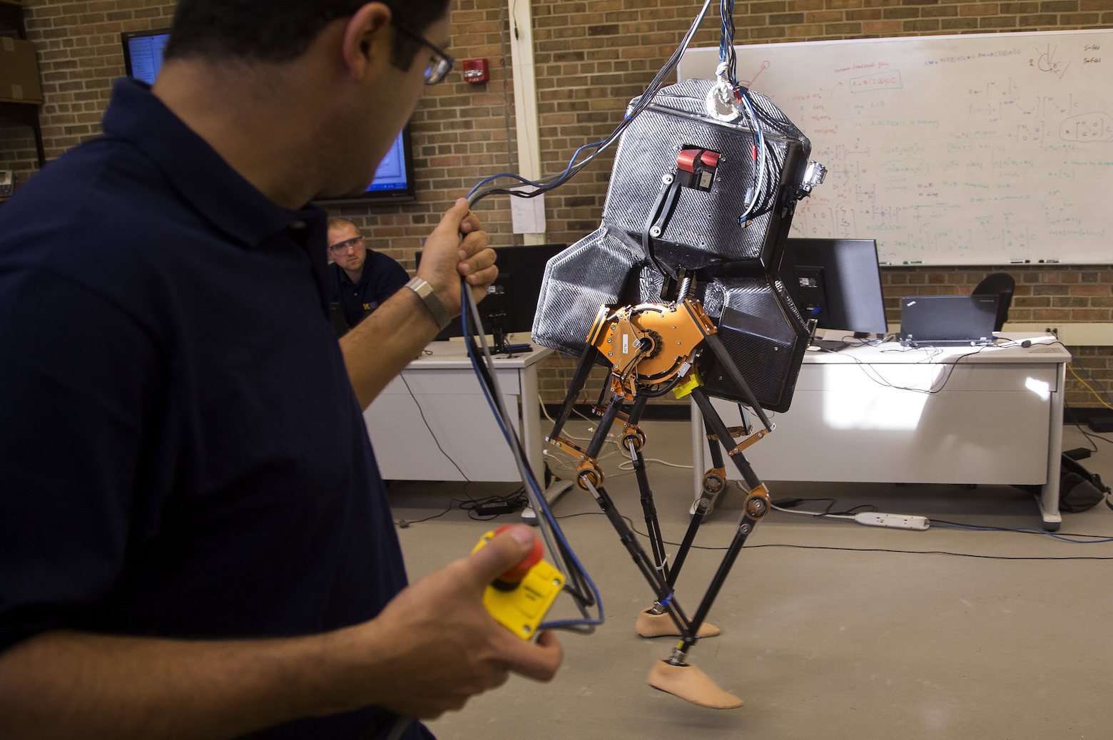 Kaveh Akbari Hamed, ECE Research Fellow, holds the stop mechanism while testing MARLO, a bipedal robot, in a lab located in the GG Brown Building on November 20, 2013.