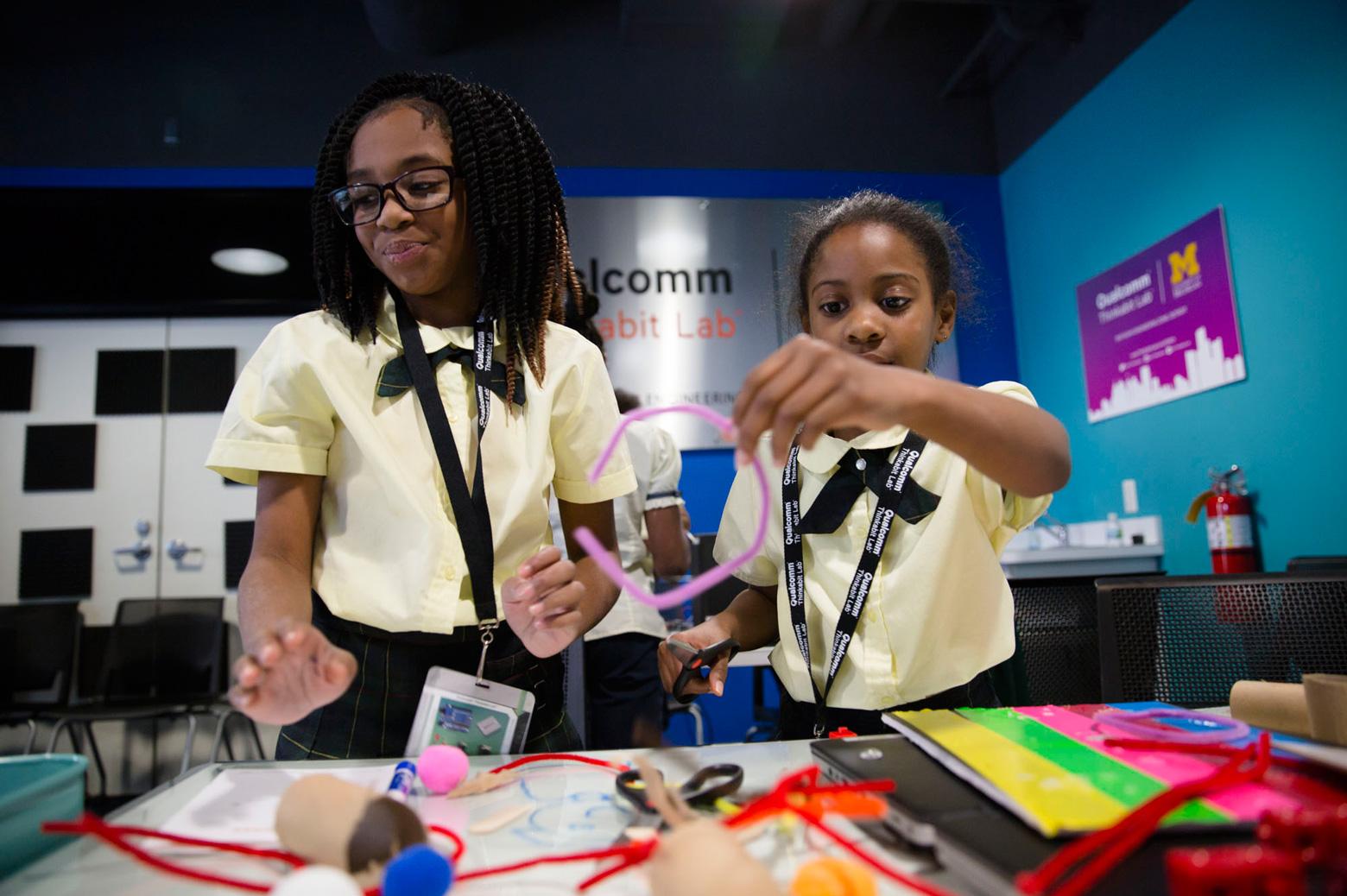 Two children work on Arduino kits