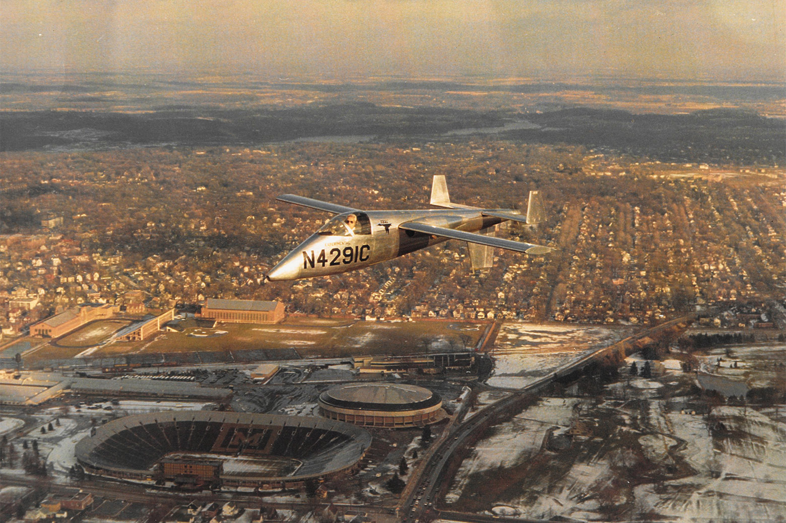 A small, unpainted metal plane with the identifier N429IC painted on the side in bold black letters is seen flying over Michigan Stadium in Ann Arbor, MI as snow looks to be melting. The photo was likely taken in the 1970s. Ed Lesher can be seen in the cockpit.