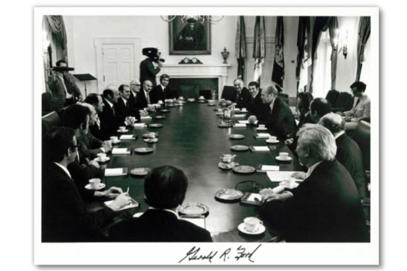 A photo of men gathered around President Gerald Ford