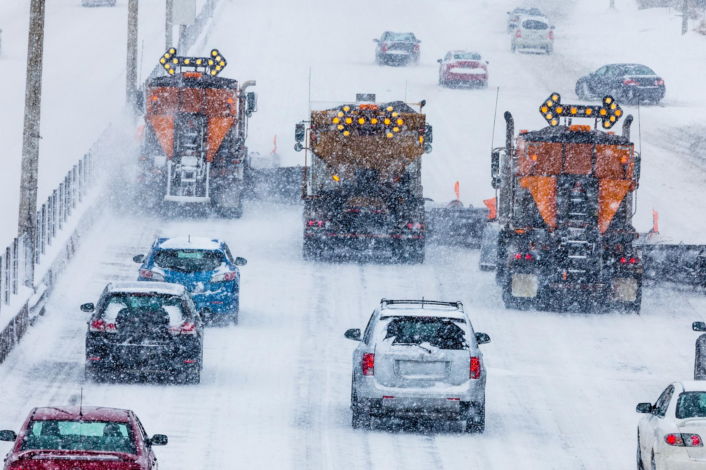 A photo of three snow plows clearing a busy highway of snow