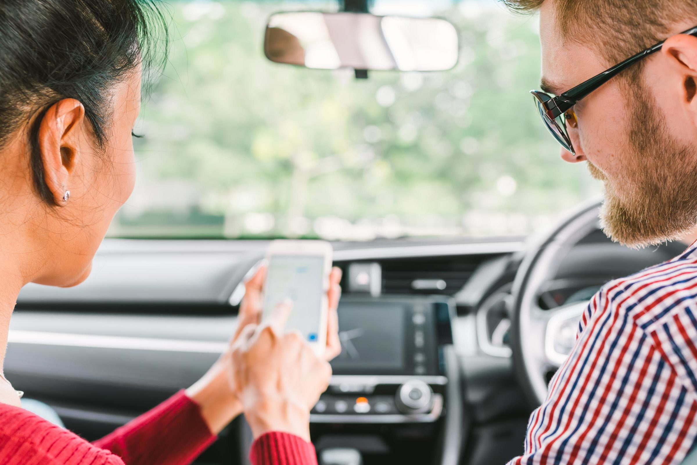 Two people in a car looking at a phone