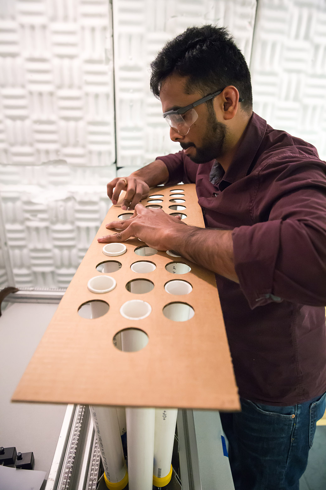 A graduate student places a rectangular cardboard sheet with a pattern of holes cutout overtop of an array of cylindrical rods.