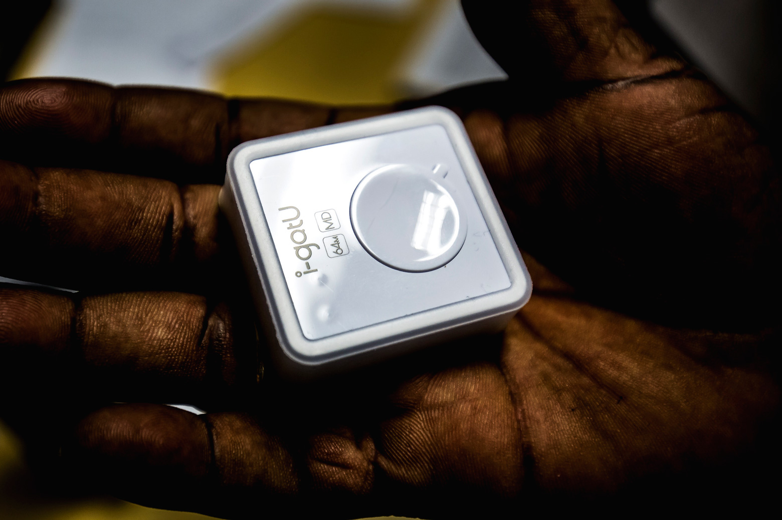 A square device sits in a human hand