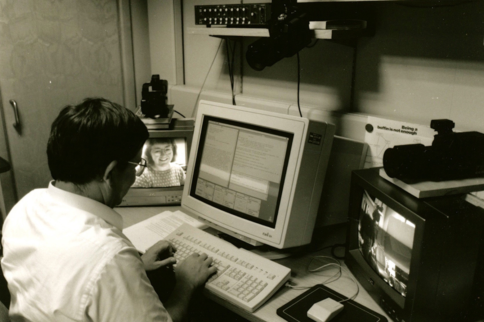 Man sitting in front of old computer doing research