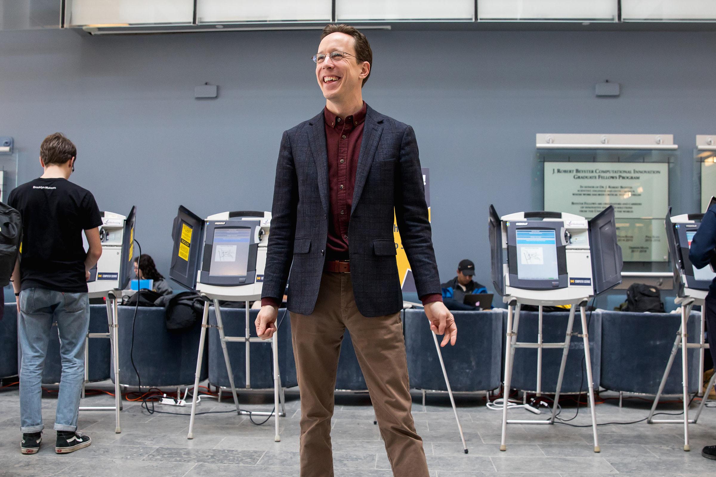 Halderman standing in front of voting machines