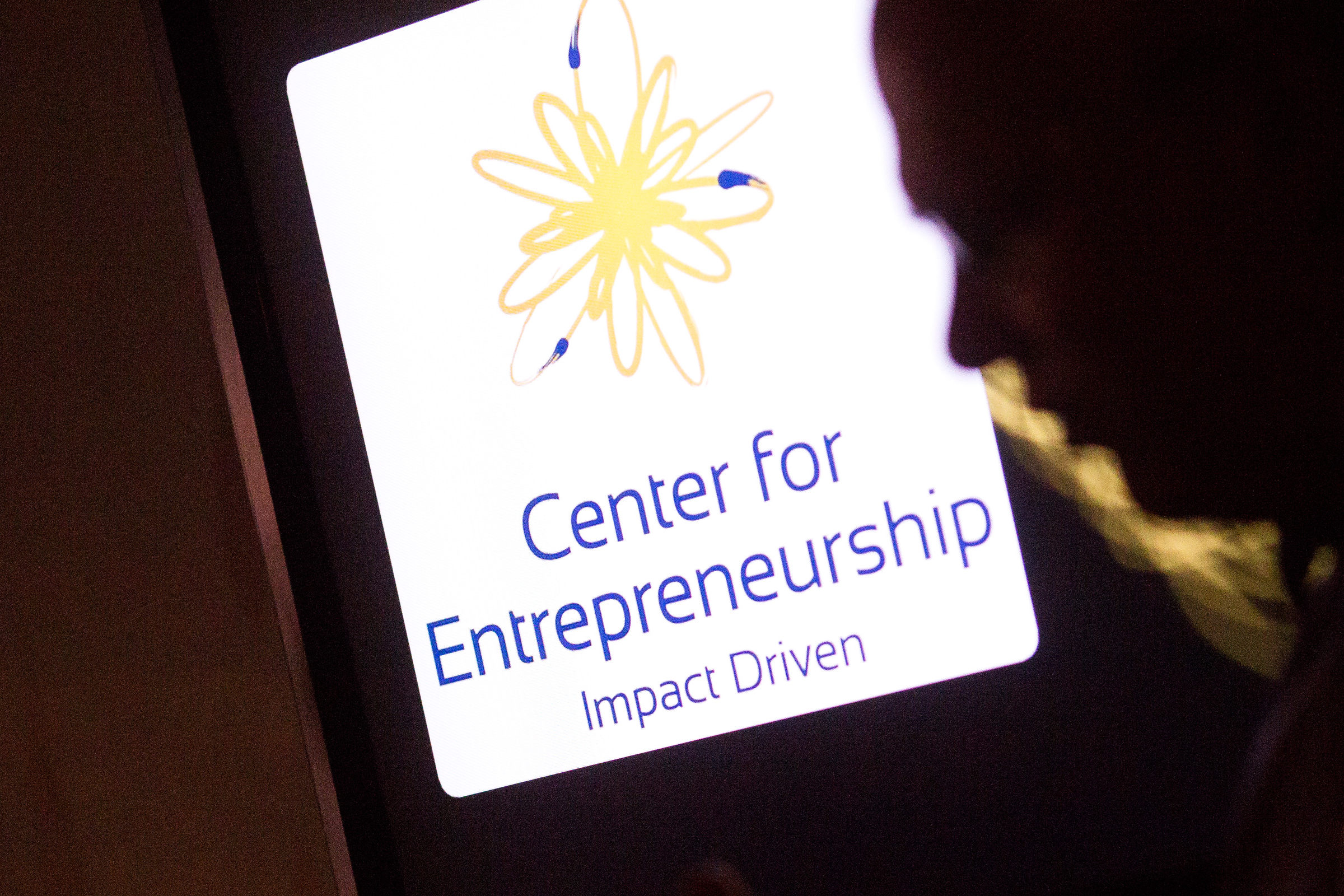 a photo of a face next to a sign for Center for Entrepreneurship