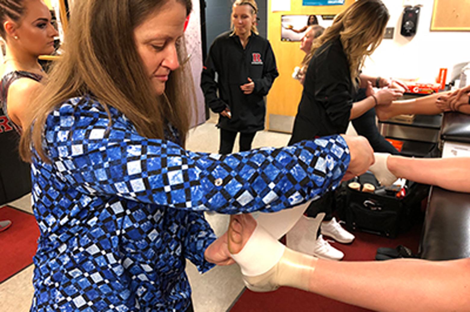 Athletic trainer wraps athlete's foot