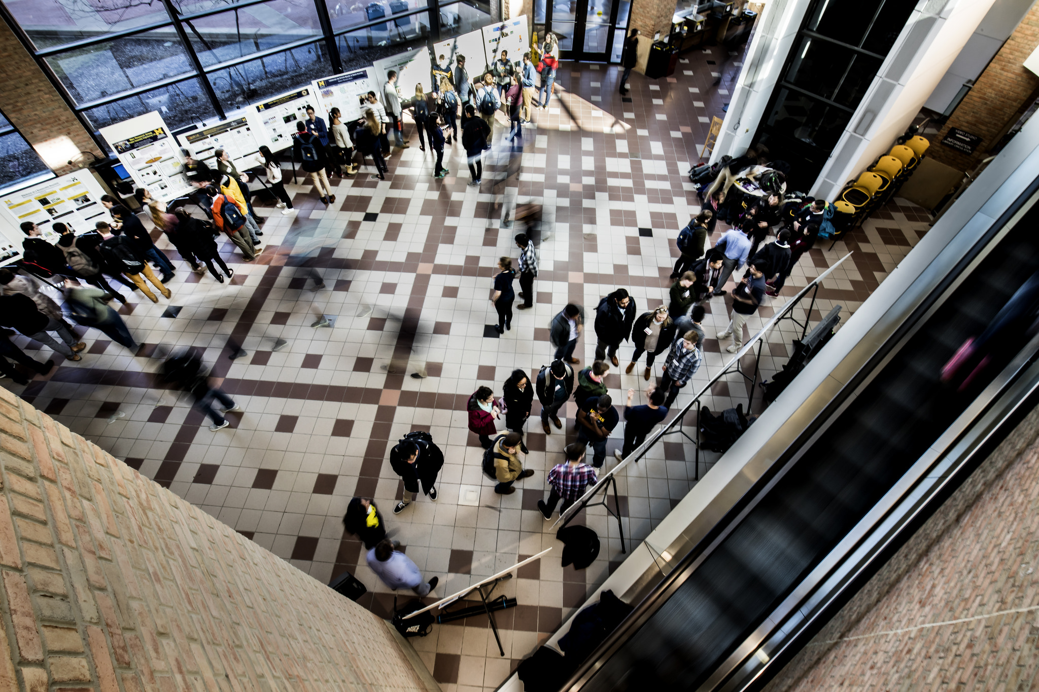 Birds-eye view of diverse students walking in atrium past posters