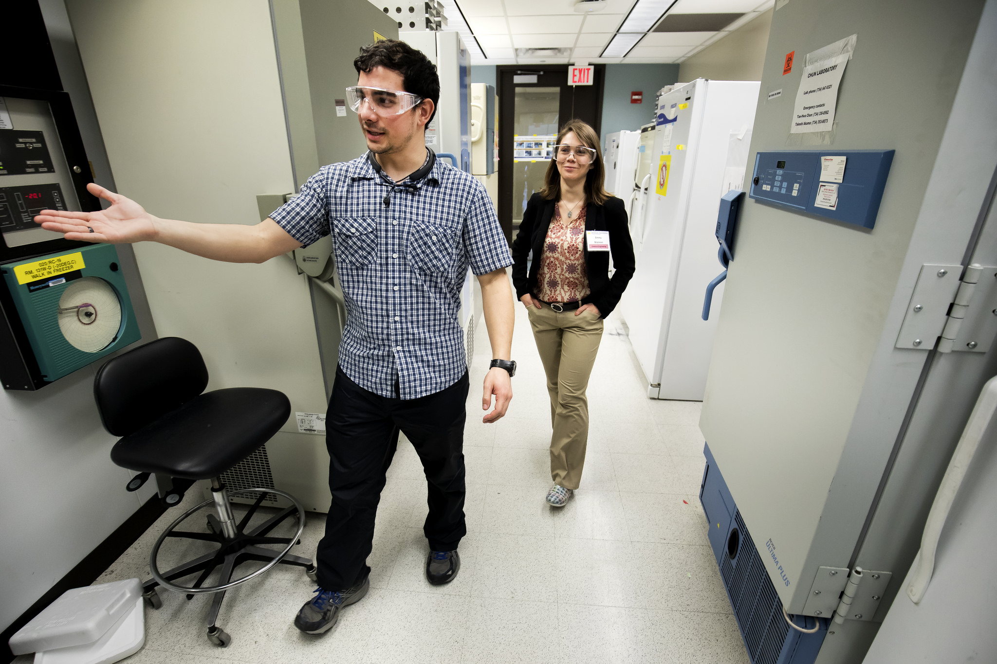 Male graduate student shows female prospective graduate student lab equipment in NCRC of the University of Michigan