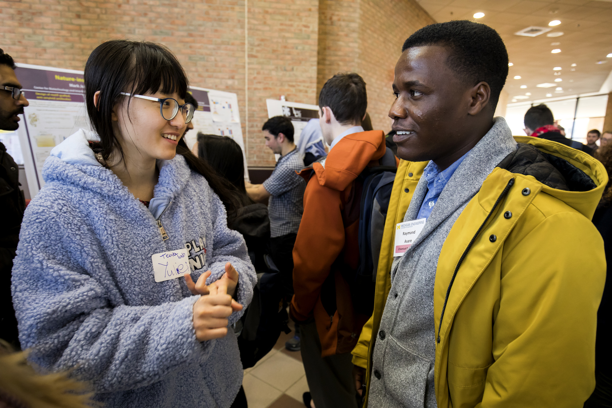 Female graduate student talks with male prospective graduate student during poster session on North Campus of the University of Michigan