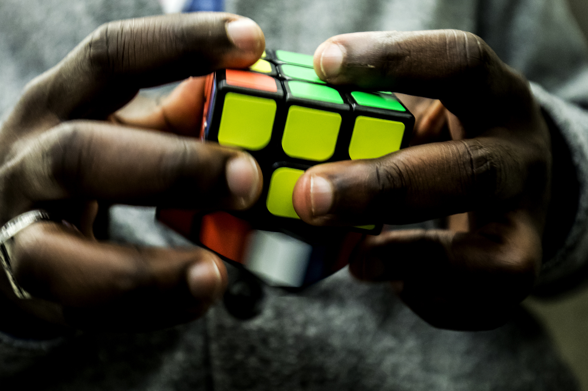 Close-up of hands rotating a Rubik's Cube