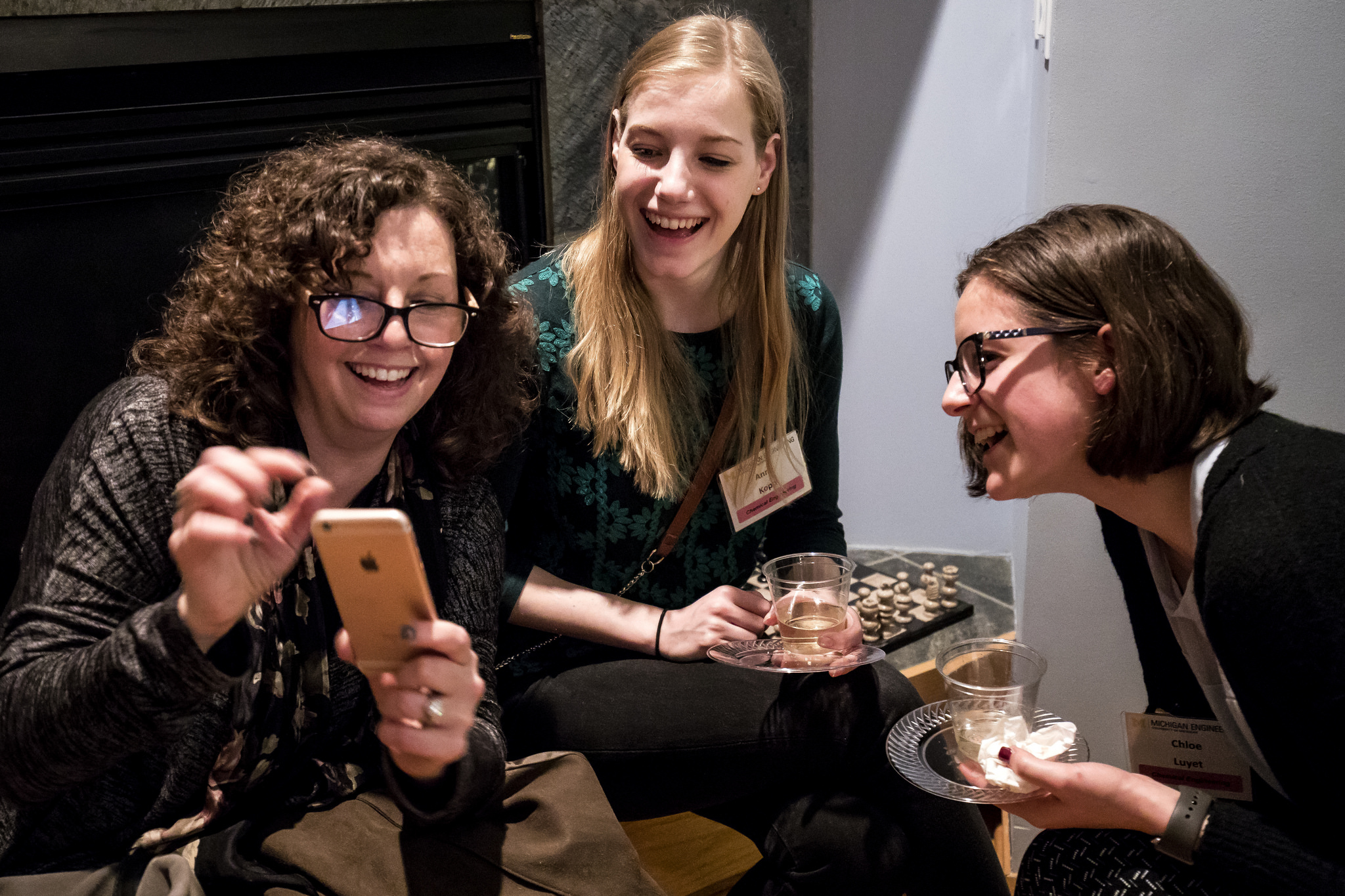 Smiling curly-haired woman shows two laughing females her phone screen