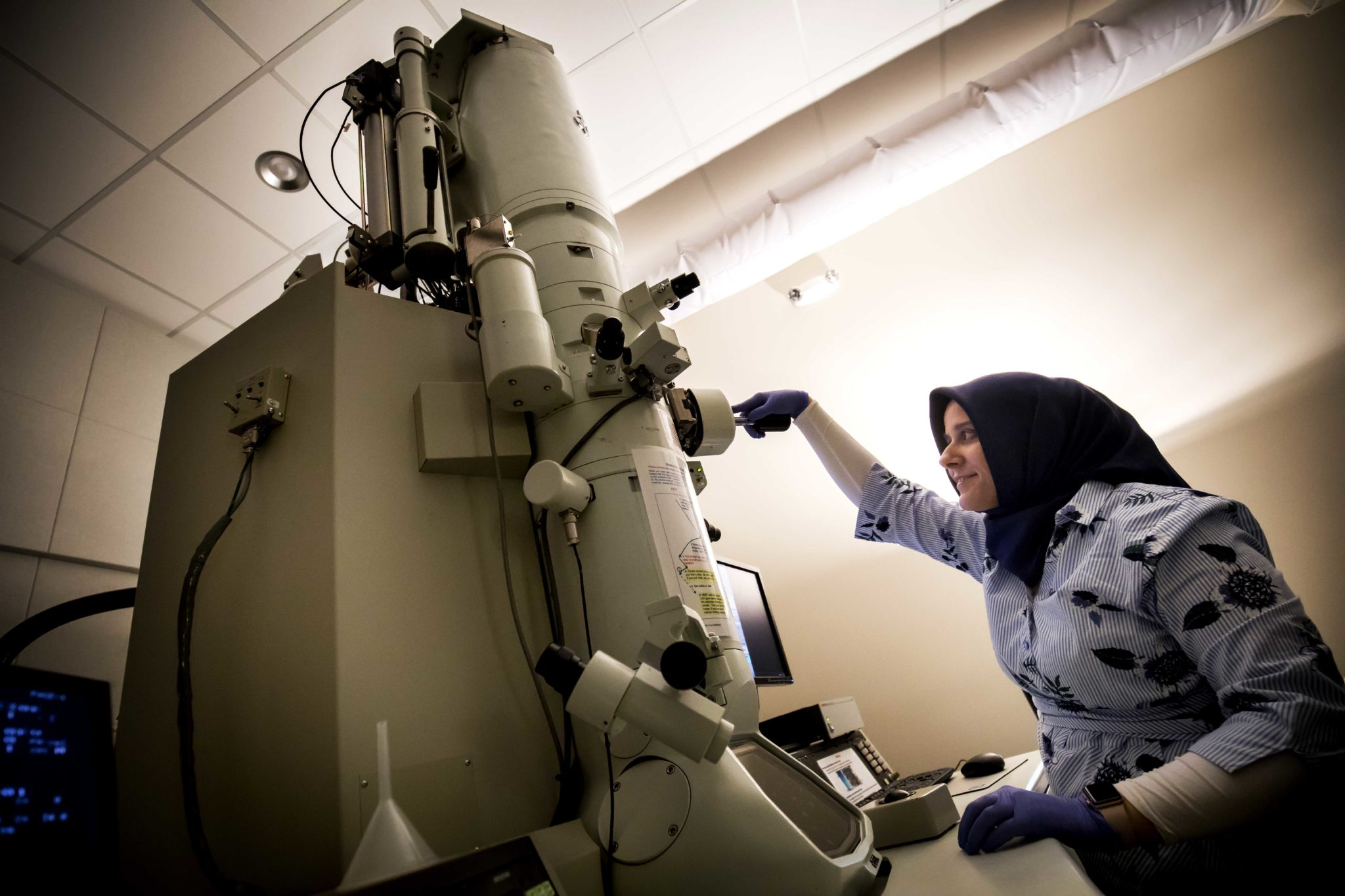 A researcher uses a transmission electron microscope to view nanoparticles.
