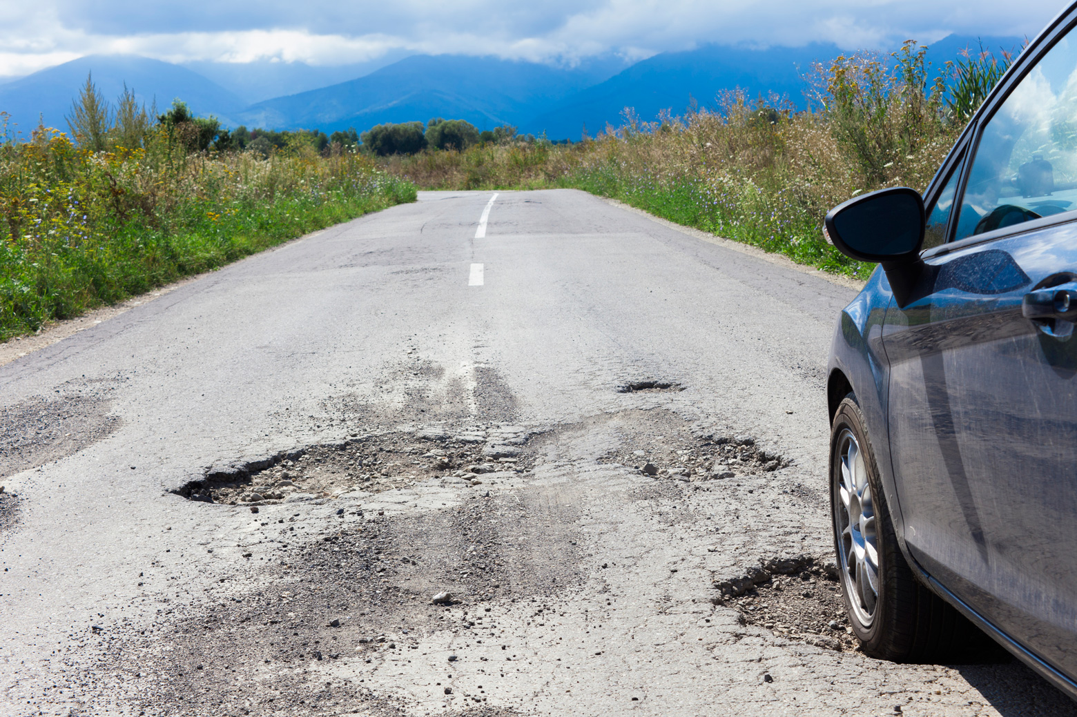 A car drives through potholes in the road