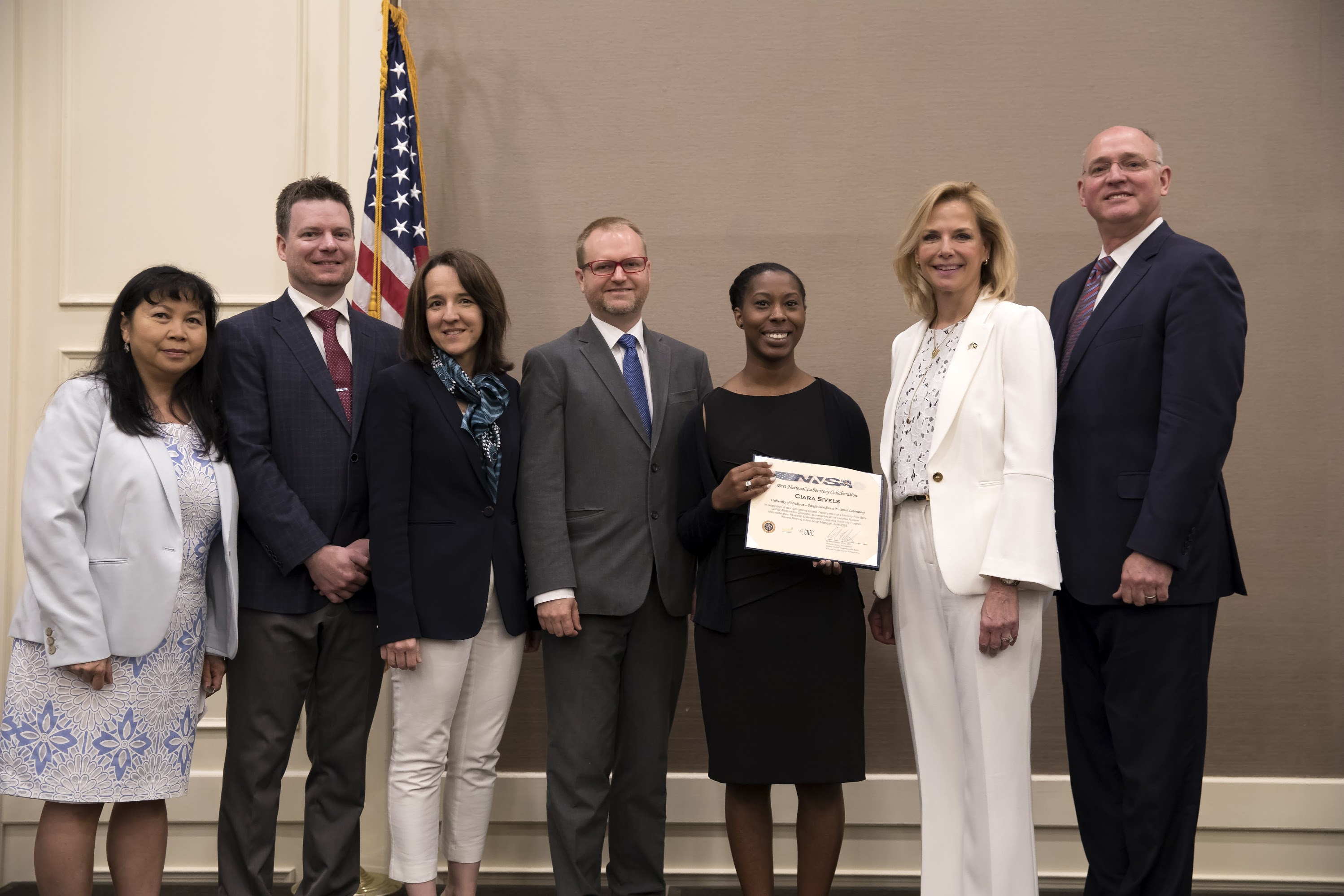 Ms. Lisa Gordon-Hagerty awards a National Laboratory Impact award to Ms. Ciara Sivels. Left to right: Dr. Victoria Franques, Dr. Shaun Clarke, Prof. Sara Pozzi, Dr. Luke Erikson, Ms. Ciara Sivels, Ms. Lisa Gordon-Hagerty, Dr. Ed Watkins.