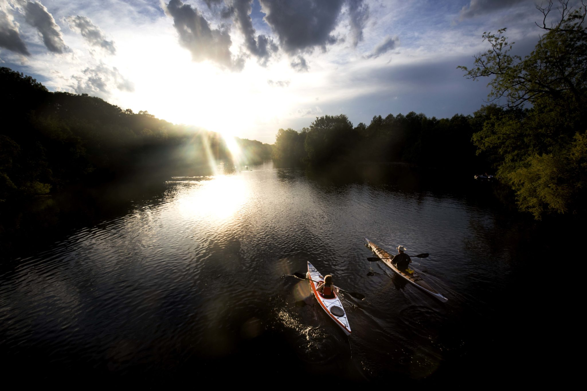 Two individuals kayak on the Huron River.