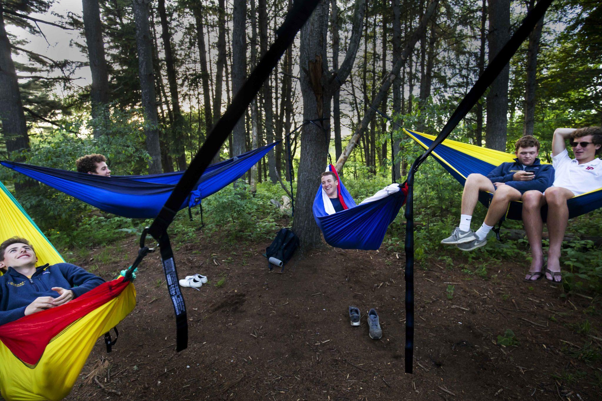 A group of Michigan Rowing team members hang in hammocks in the Nichols Arboretum.