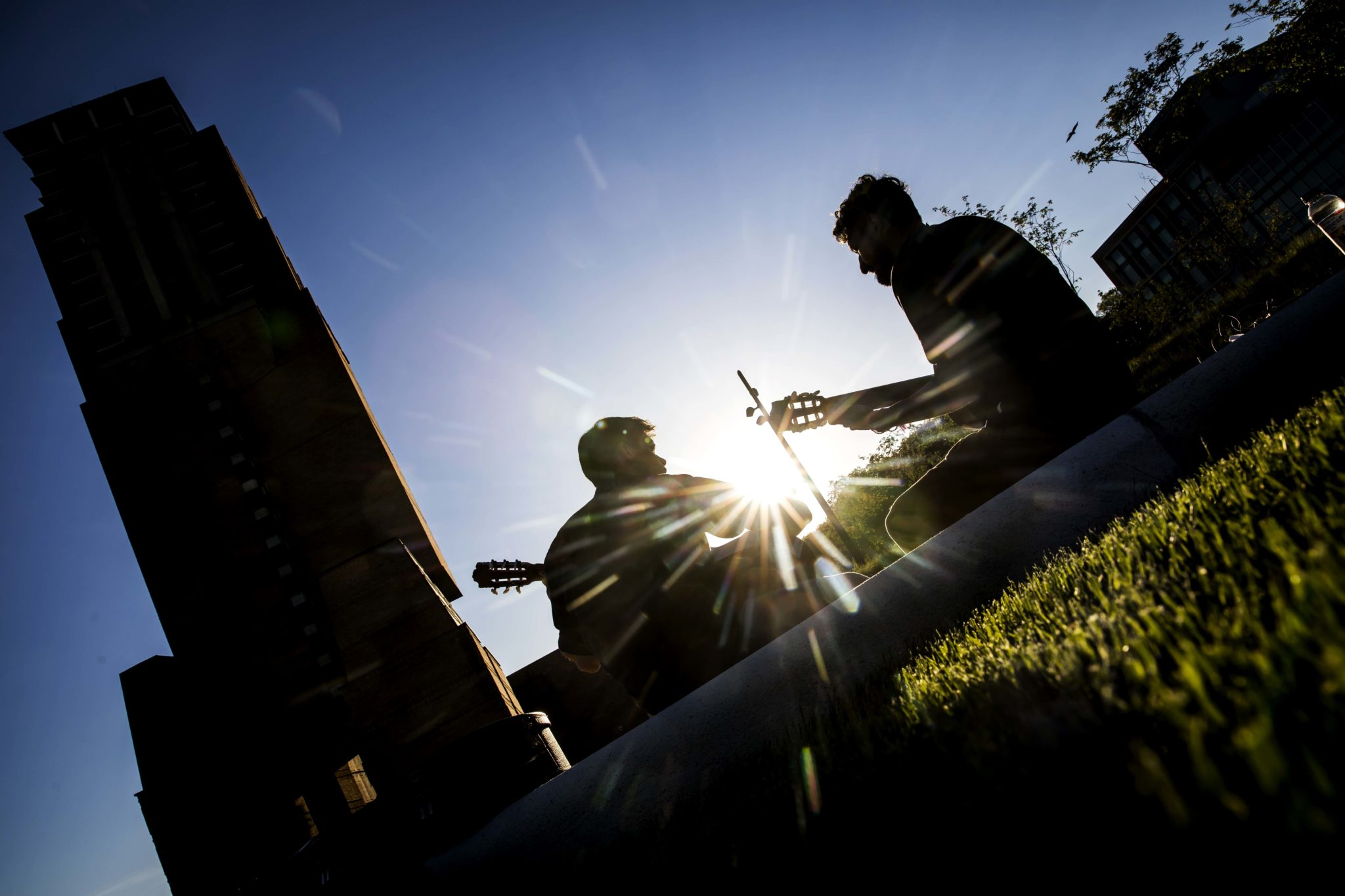 Two graduate students play guitar on the Eda U. Gerstacker Grove.