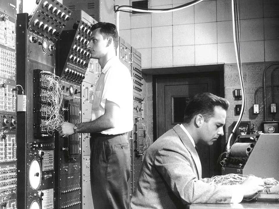 A black and white photo of two men working on computers