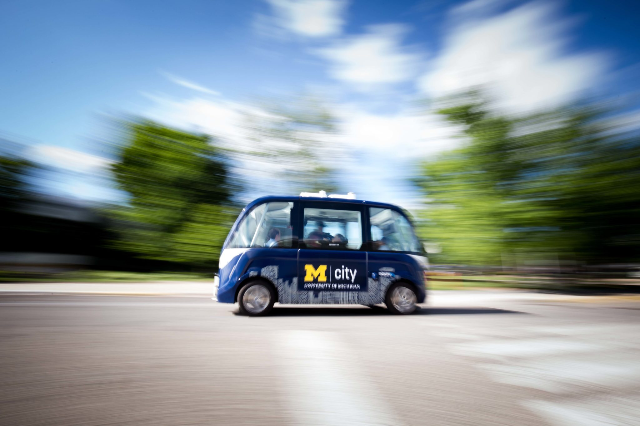 An autonomous shuttle drives in front of the North Campus Research Complex