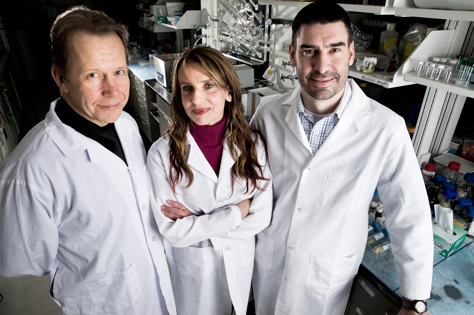 Nicholas Kotov, Angela Violi, and Scott VanEpps stand together in the lab