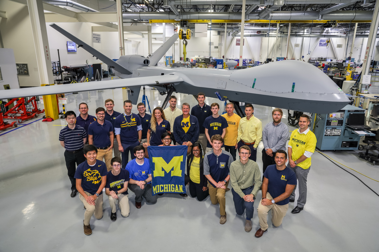 Michigan interns stand with Michigan alumni at GA stand in front of a MQ-9 Reaper (Predator B).