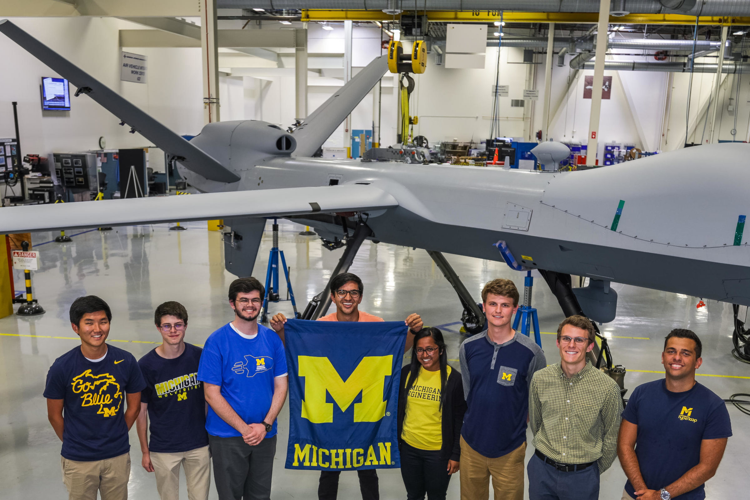 GA interns (from left to right) Dennis Park, Diego Toral, Henry Beh, Harsh Jhaveri, Amy Joseph, Dan Ferriero, Philip Wdowiak, and Alex Laporte stand in front of a MQ-9 Reaper (Predator B).