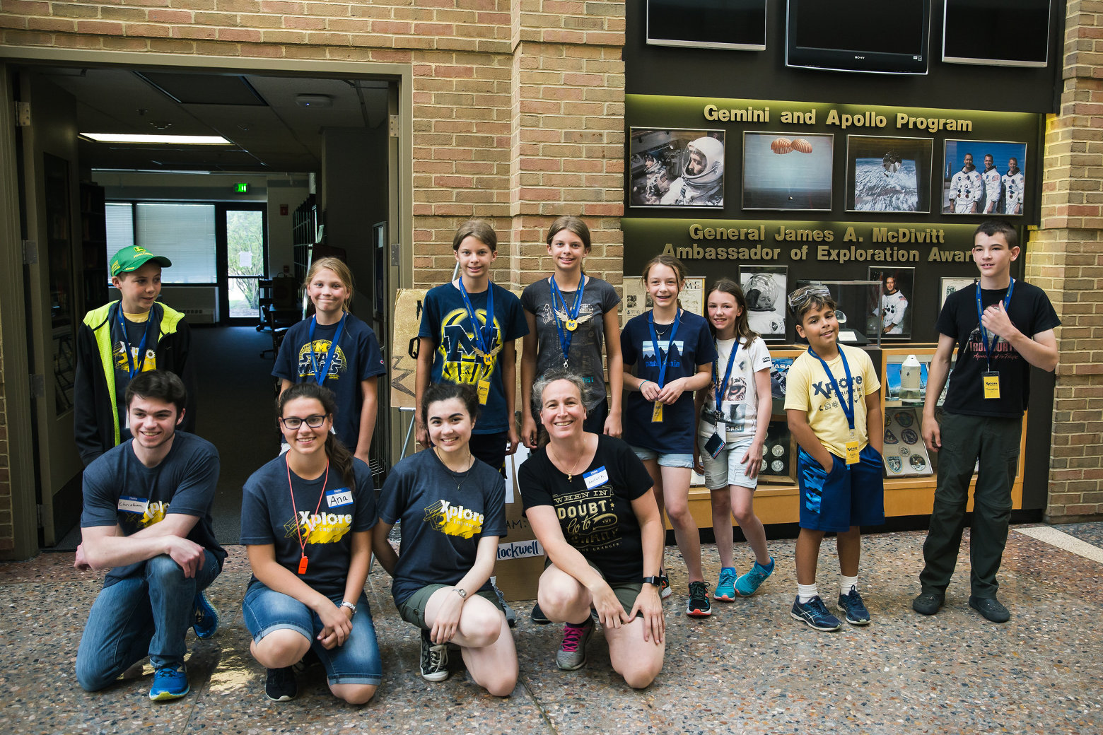 Ana Timoficiuc (bottom, second from left), Sabrina Olson (bottom, third from left), and Professor Girard (bottom, fourth from left) pose for a group photo with students participating in Quidditch tournament.