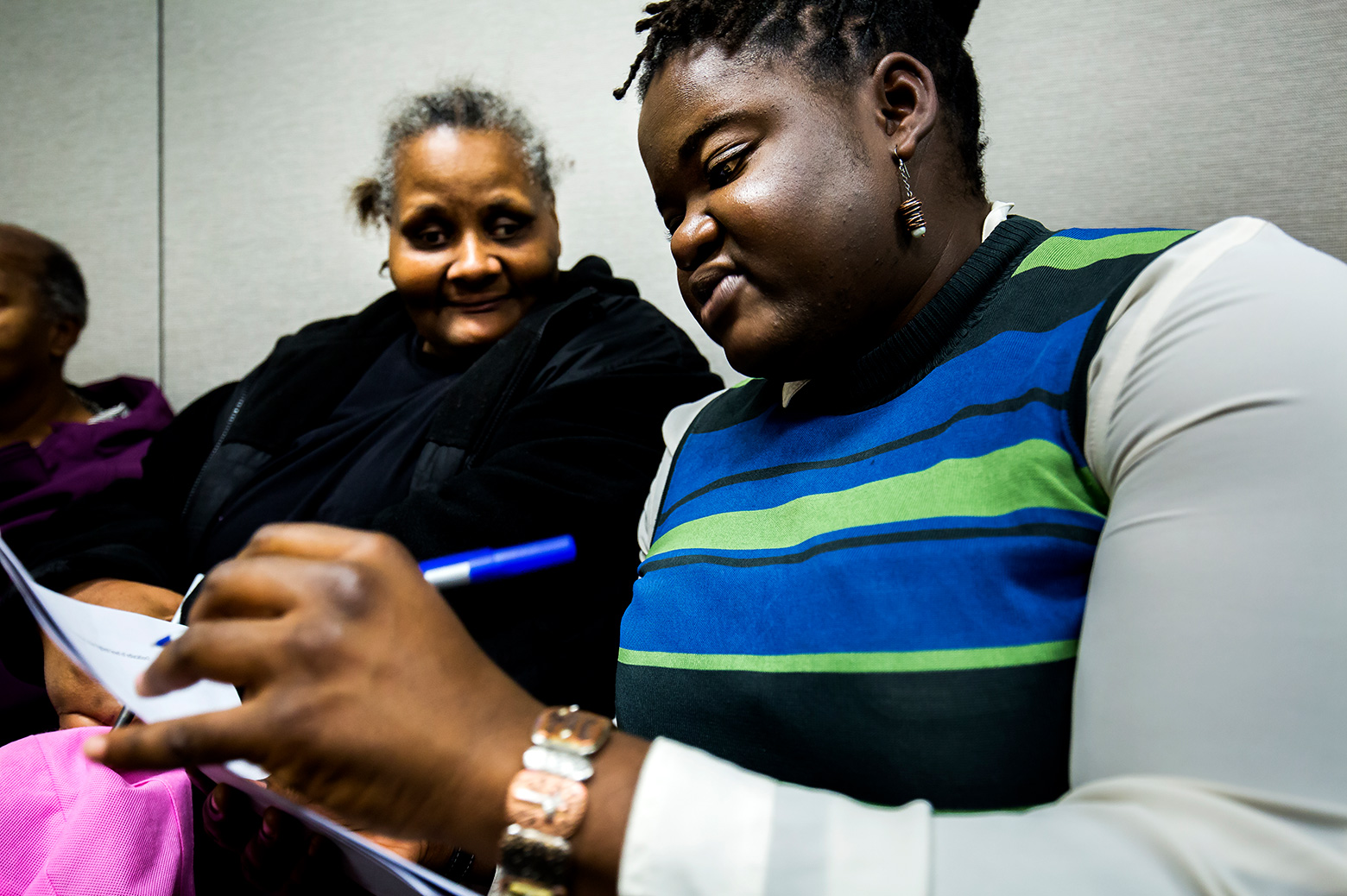 Assistant Professor Tierra Bills writing on a paper and sitting with a Benton Harbor resident.