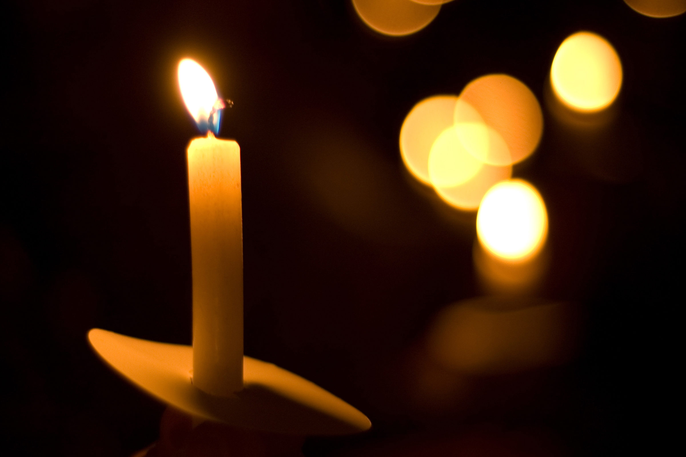single candle on a dark background with points of light in the distance