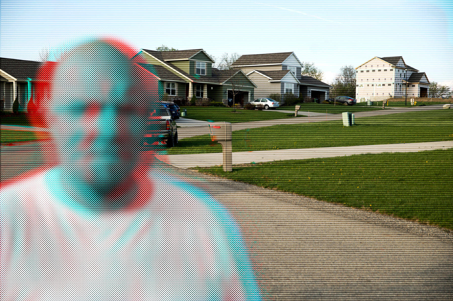 A pixellated man stands in front of a suburban neighborhood