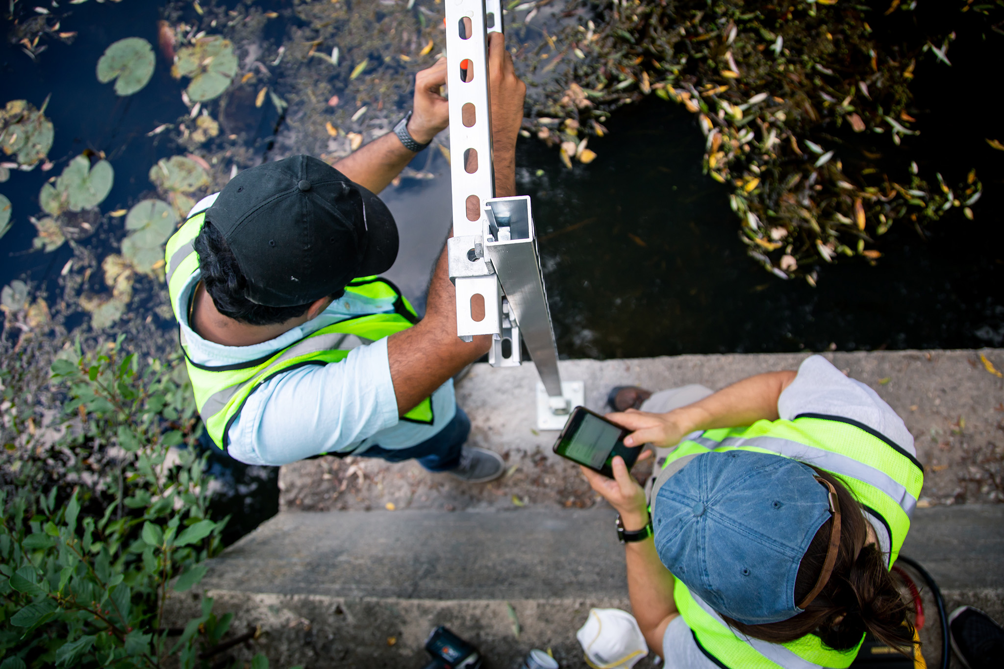 An overhead photograph of two graduate students wearing baseball caps and safety vests as they stand on a concrete ledge next to a body of water and install a metal stand for a stormwater sensor.