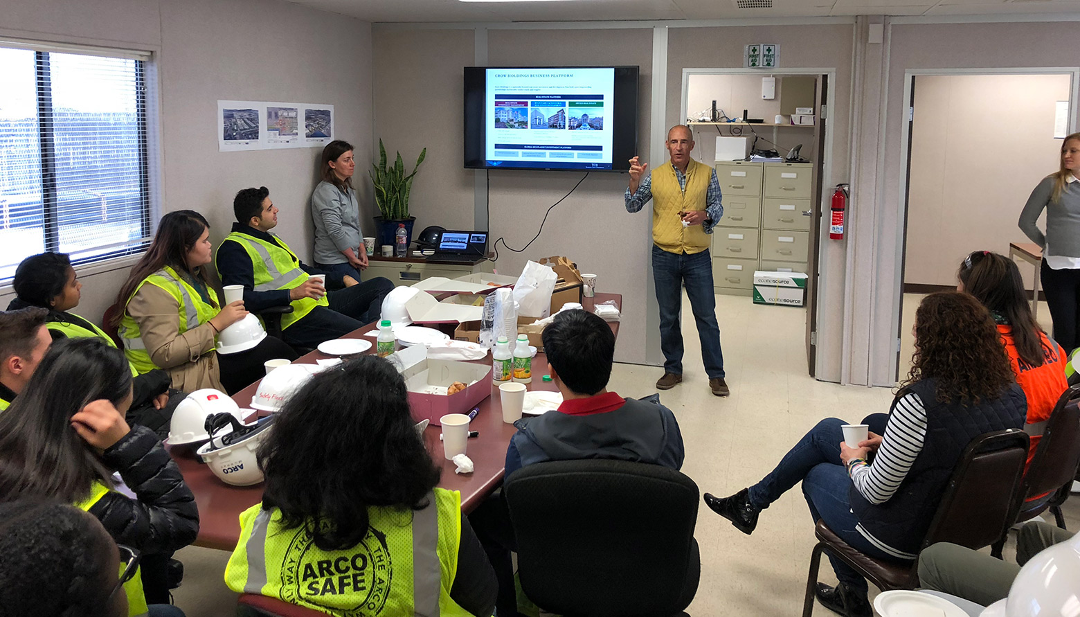 Man giving presentation to small group in construction office