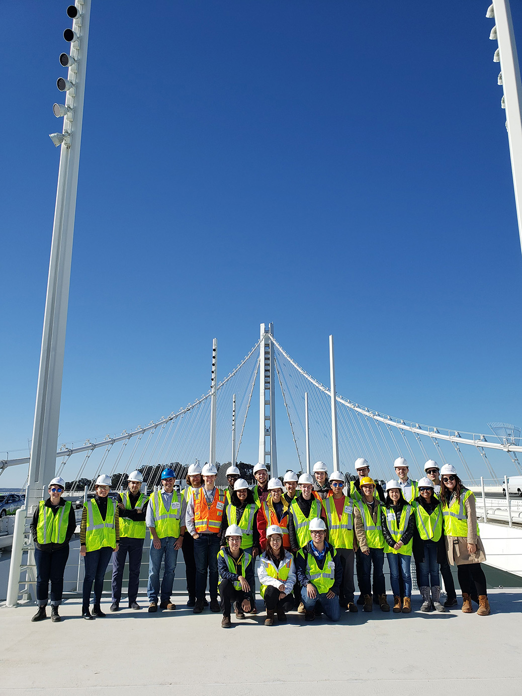 People in hard hats and safety vests pose on a white bridge with blue sky in the background