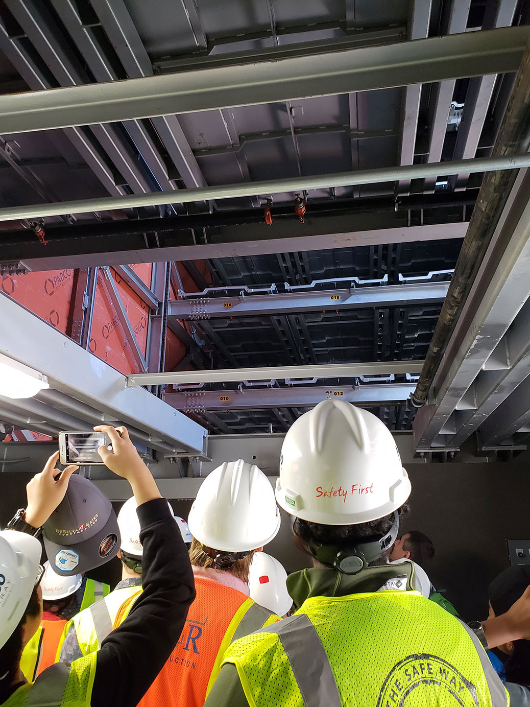 People in hard hats and safety vests view densely packed parking spaces in an automated parking structure
