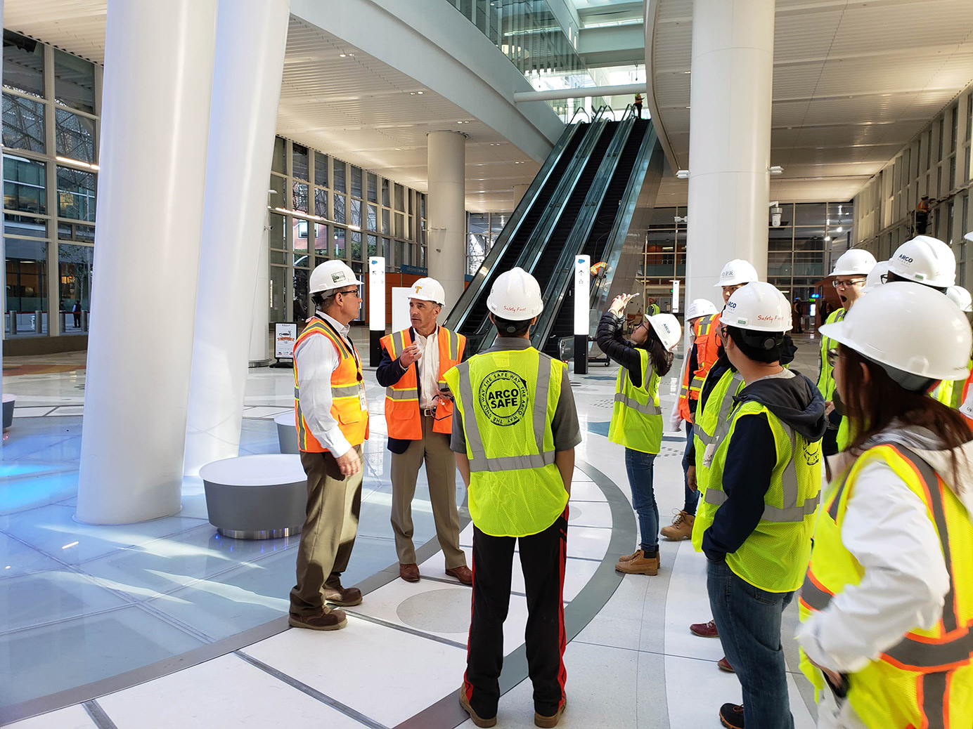 People in hard hats and safety vests stand in a modern building
