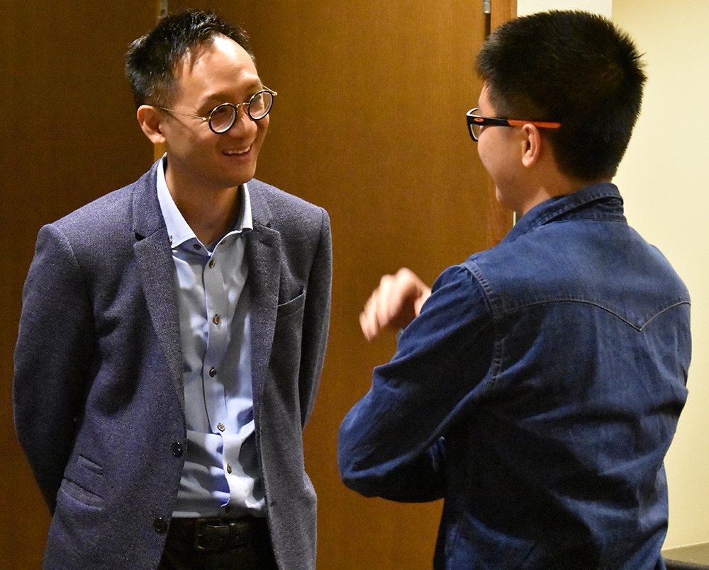 Tong chats with a student after his presentation.