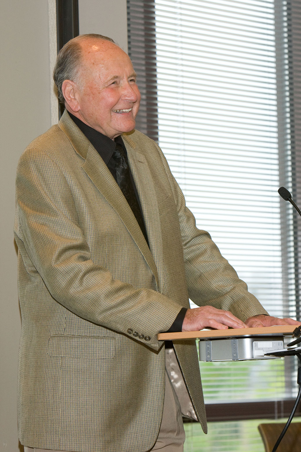Man standing at a podium and smiling