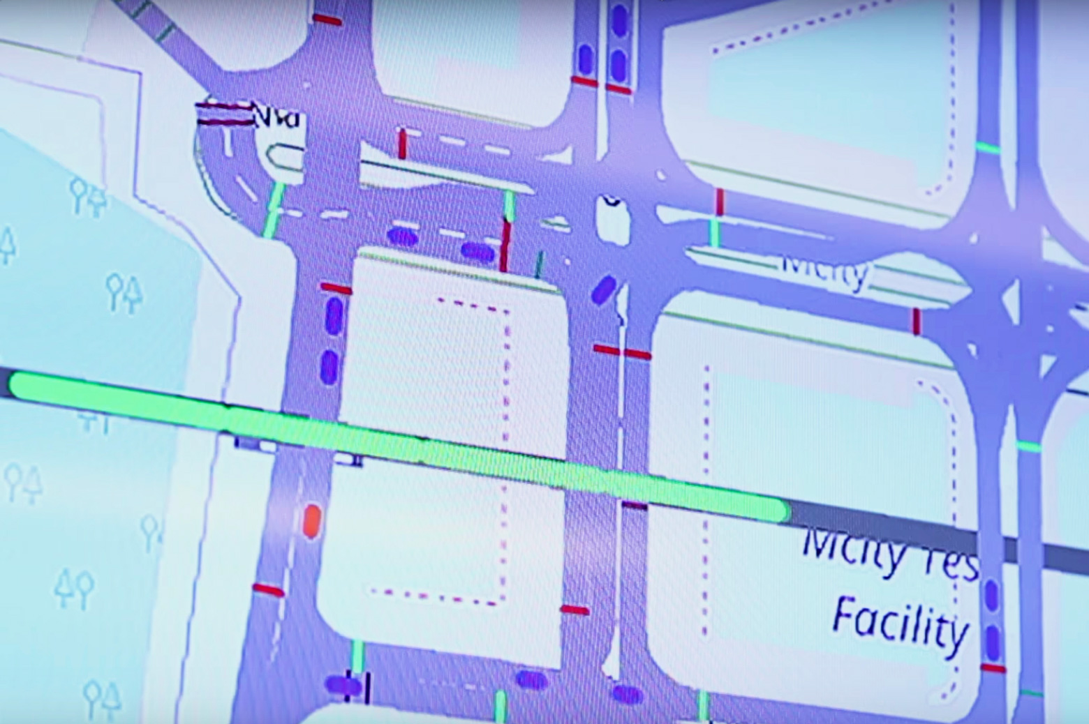 An image of the screen in the Michigan Traffic Lab while a virtual train (in green) travels through a rail crossing at Mcity. Real (red) and simulated vehicles (blue) react. Credit: Screen capture from a video by Mike Wood