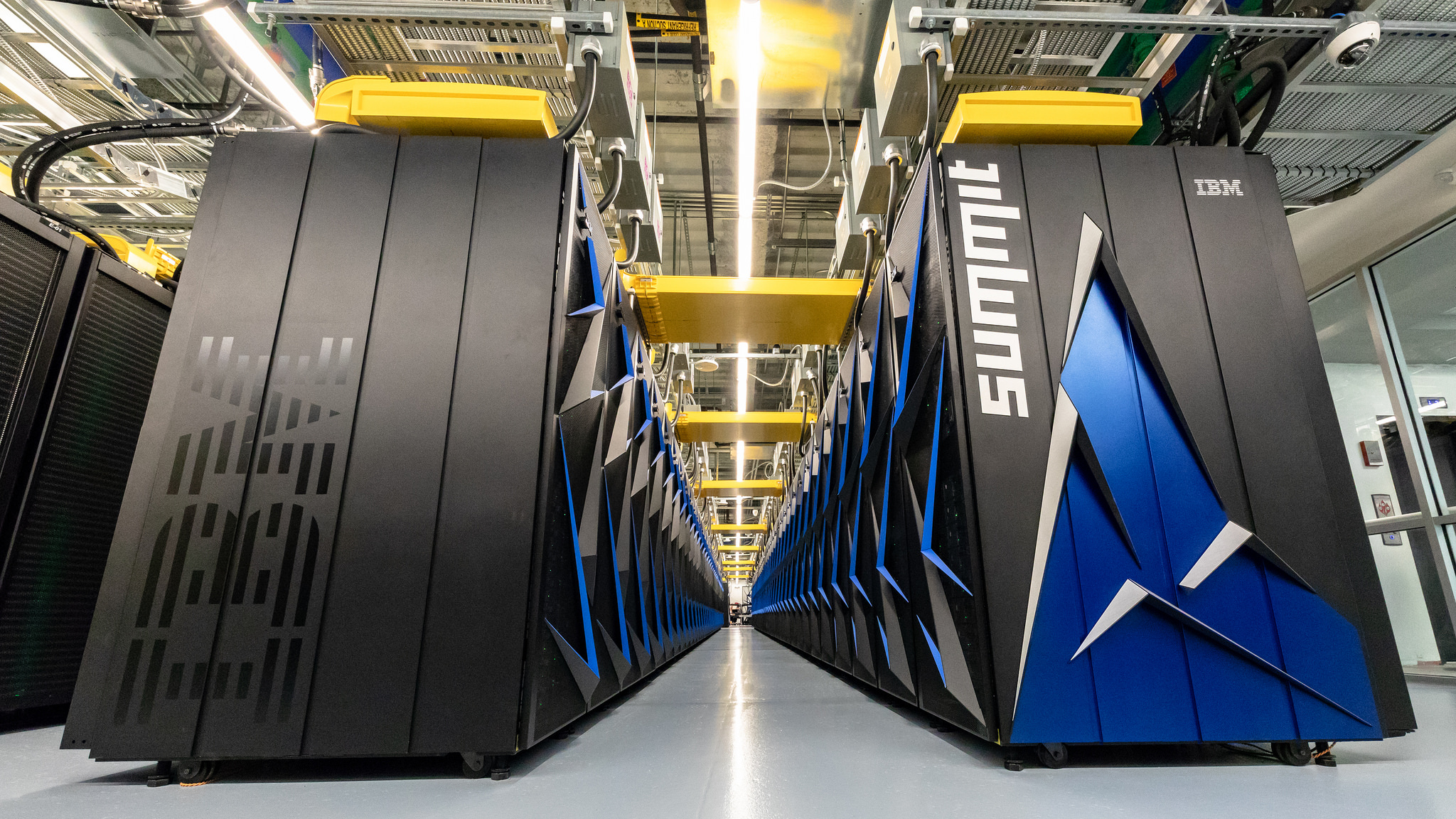 Two rows large black boxes contain supercomputer inside industrial space