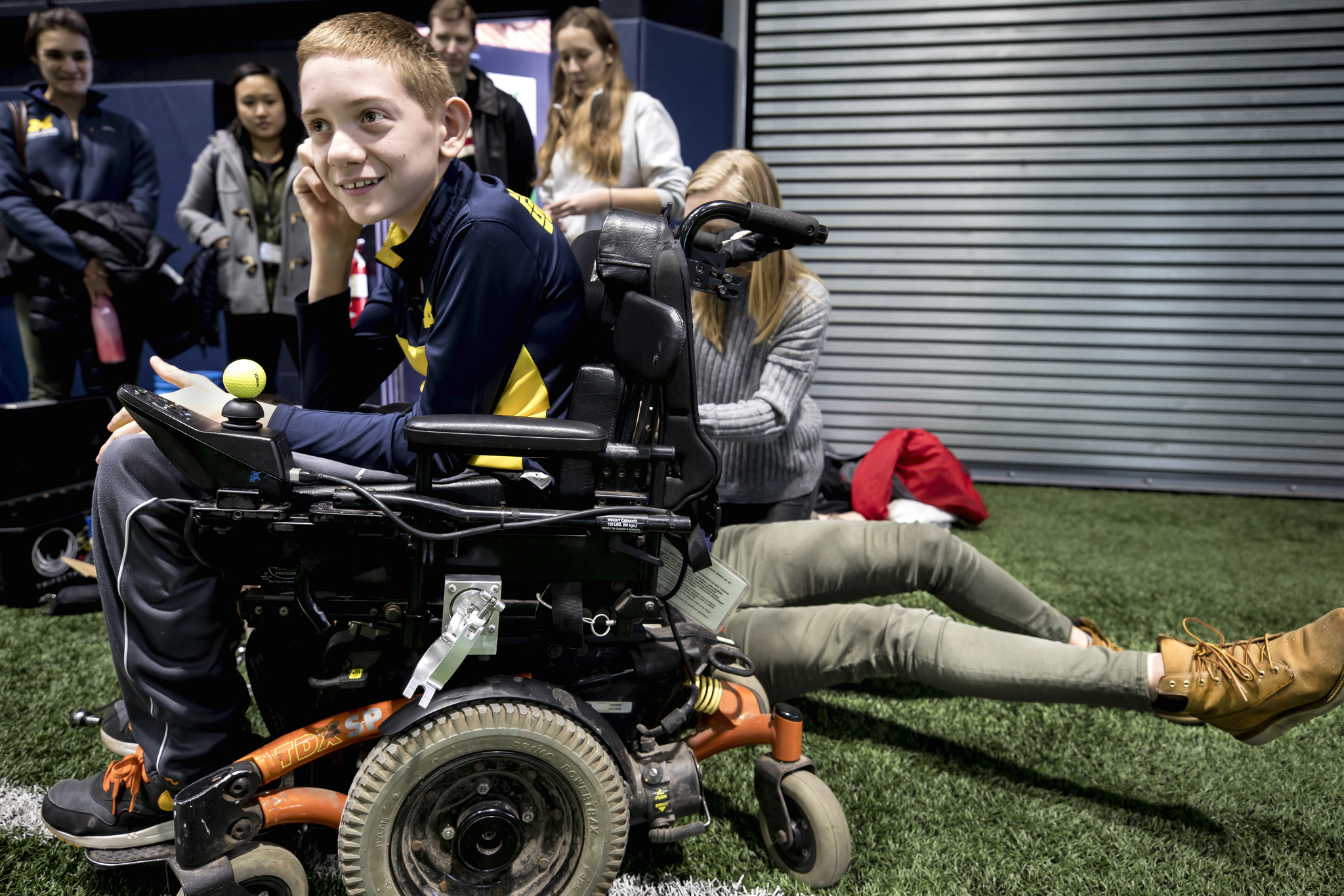 A photograph of Braden Gandee receiving an installation onto his wheelchair.