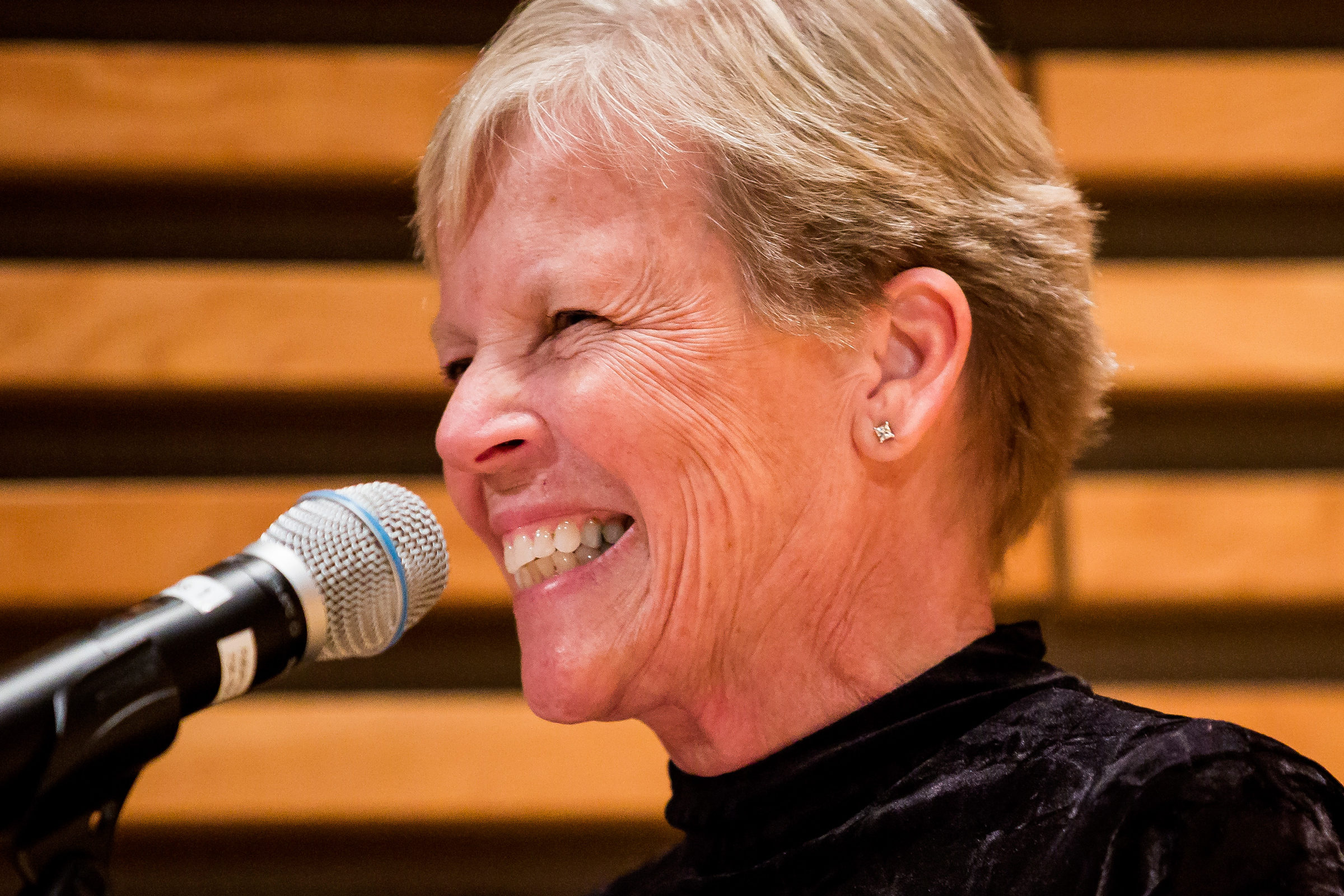 Jeanne Murabito smiling behind a microphone
