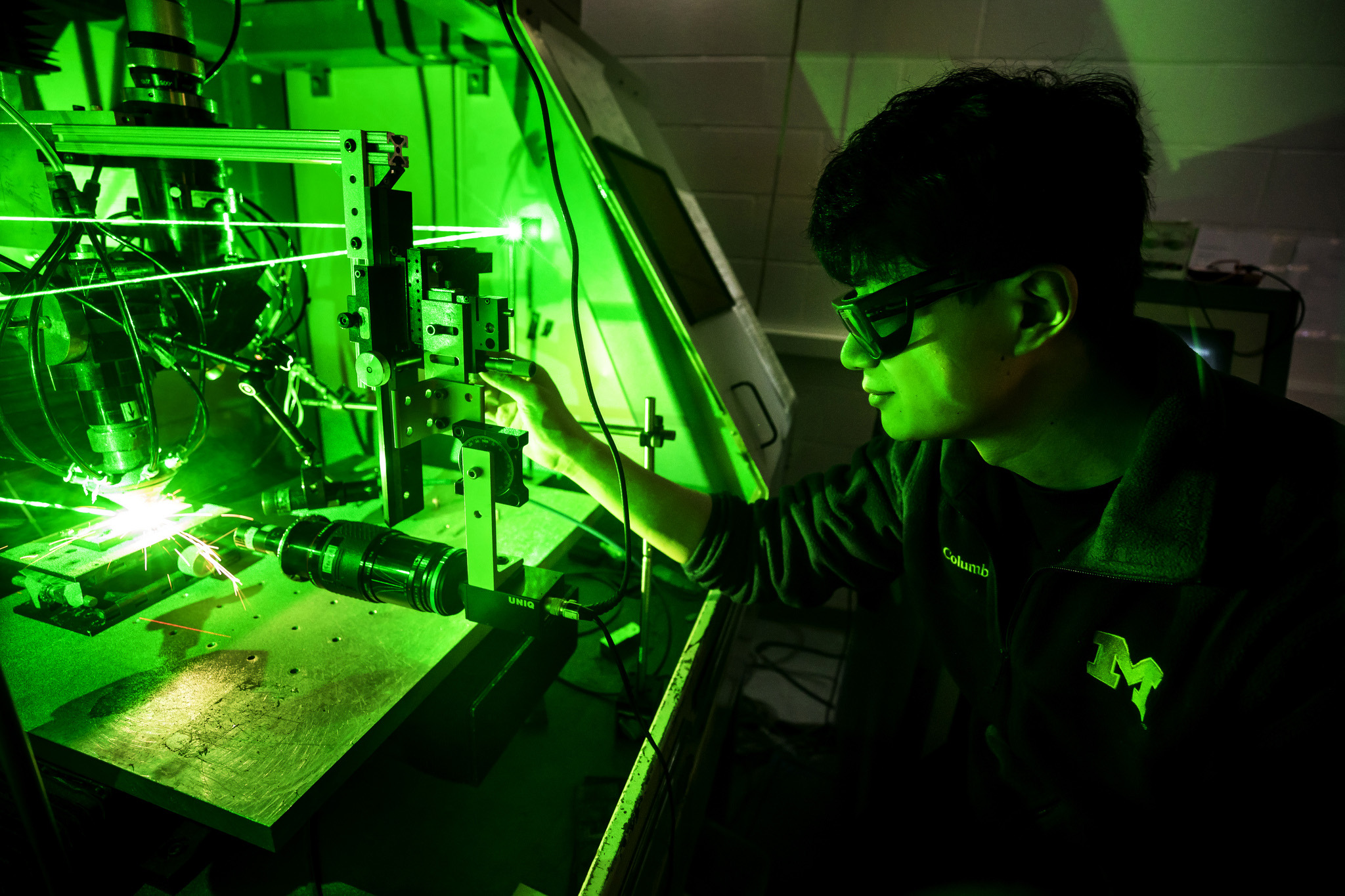 A photograph of graduate student in lab running a laser deposition system.