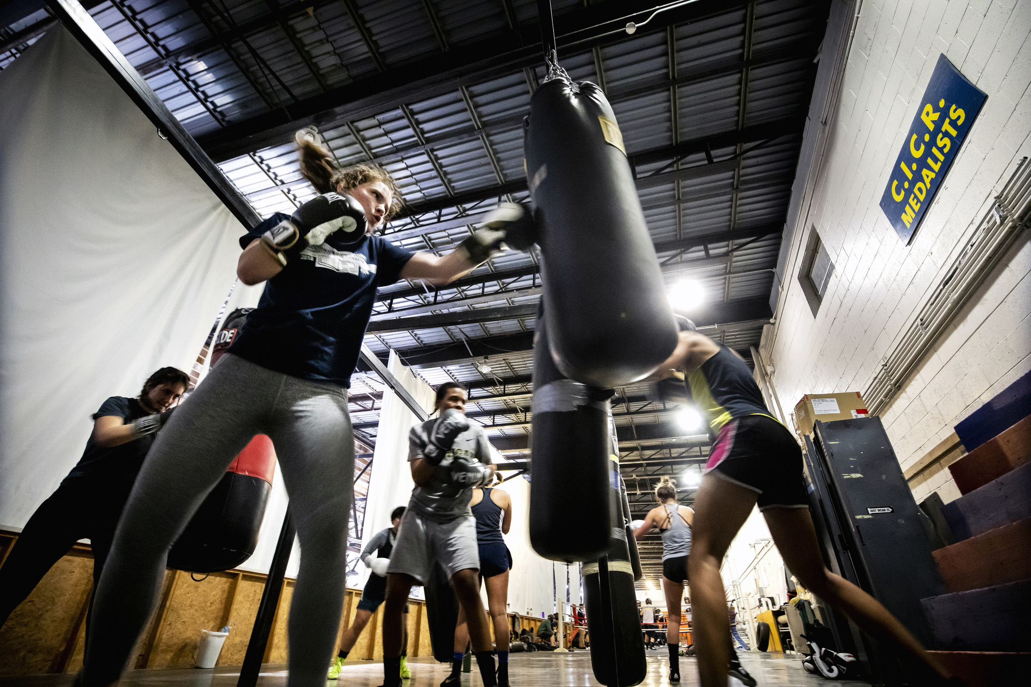 A photograph of Michigan Engineering students punching bags during a UM Boxing Club practice.