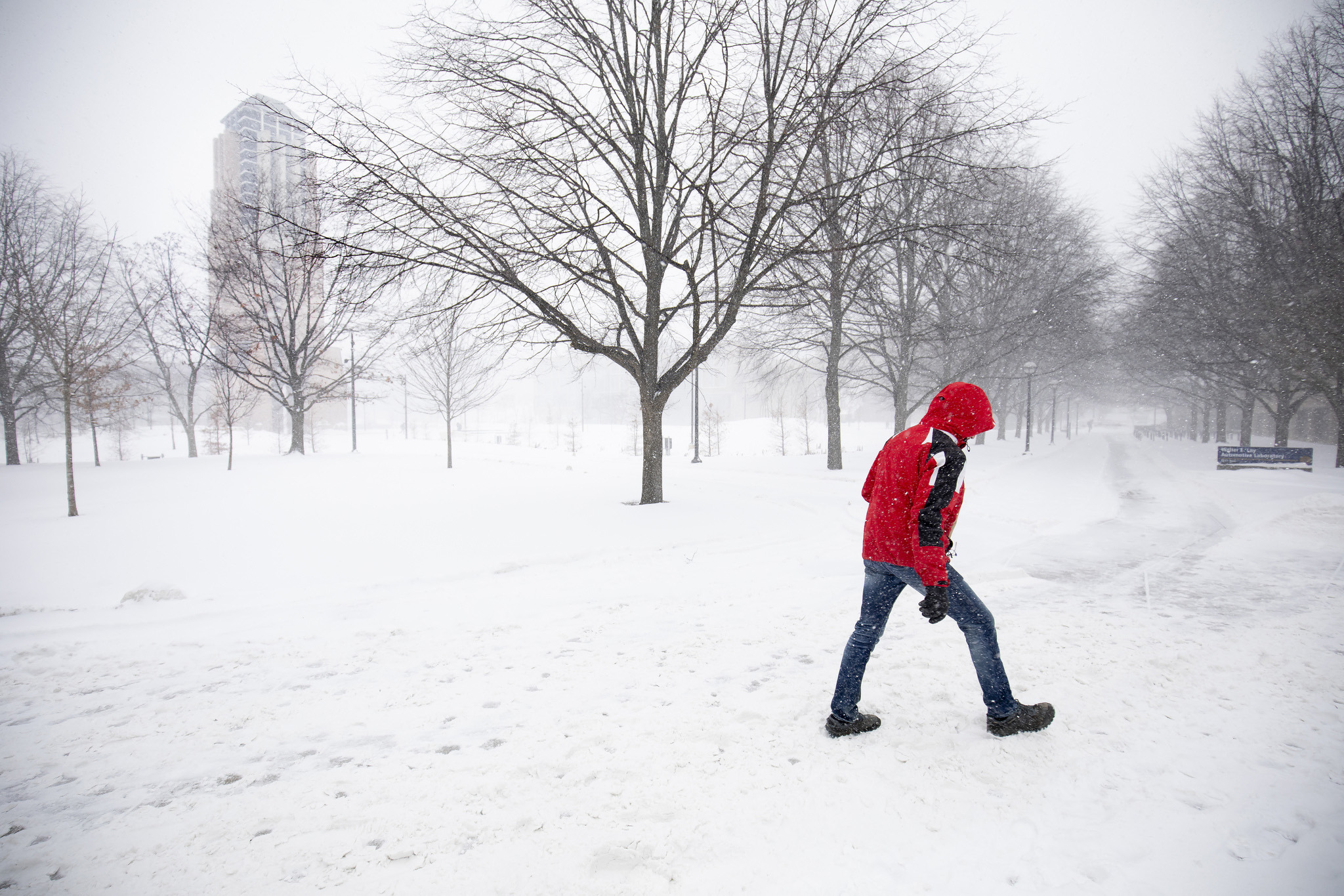 A photograph of a person walking through the snow on North Campus of the University of Michigan in Ann Arbor, MI